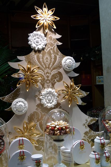 Inspiration for Christmas window displays with white and gold ornaments used for visual merchandising.