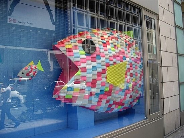 Big fish chasing a little fish, with vibrant colors. Window display in Ginza, Tokyo, Japan.