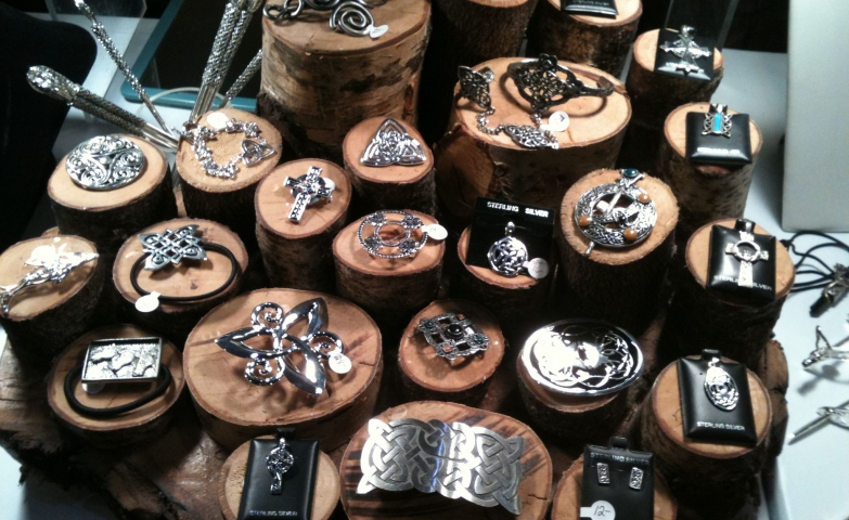 Celtic themed jewelry pieces displayed on cylinder wood bases.