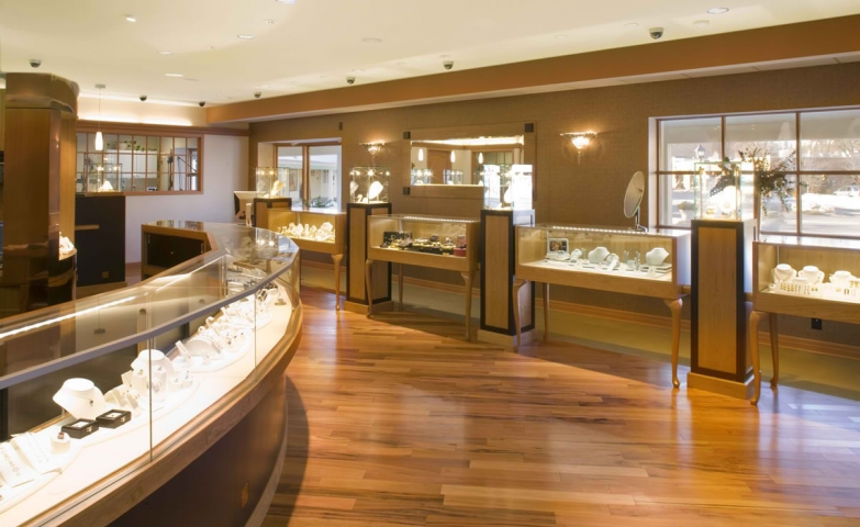 Glass boxes for jewelry display with wooden furniture in a jewelry store.