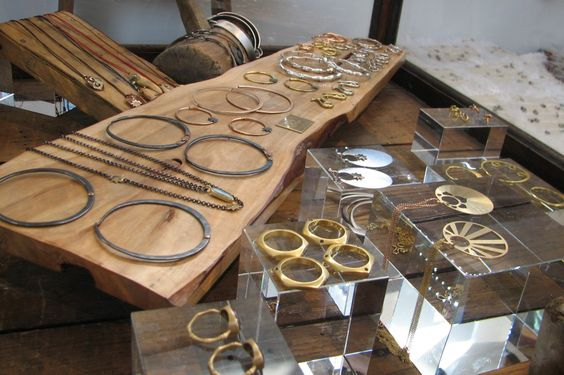 Interesting jewelry pieces displayed on wood bases and racks, and glass cubes.