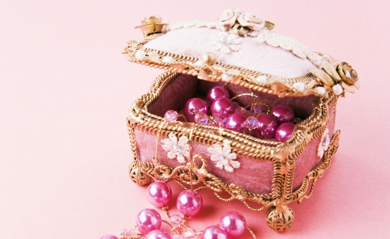 Amazing small jewelry box with gold chains, pink exterior and flower ornaments on top.