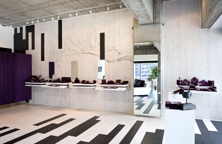 A jewelry exhibit made in a modern and stylish place, a room with contrasting black and white wooden strips and dark lilac decor.