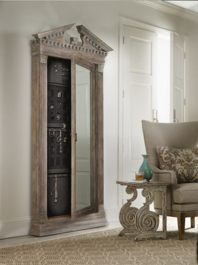 Tall wall mounted jewelry armoire made from wood with a glass door.