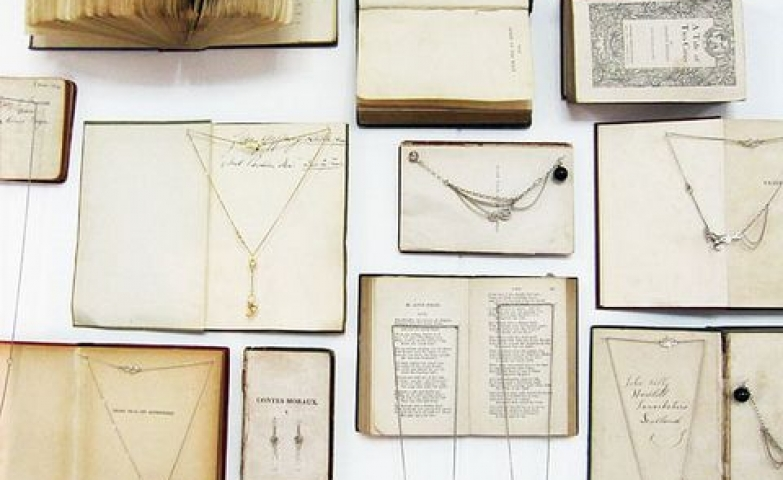 Various old books hanged on a wall in random positions and used to hang and display necklaces, bracelets and earrings.