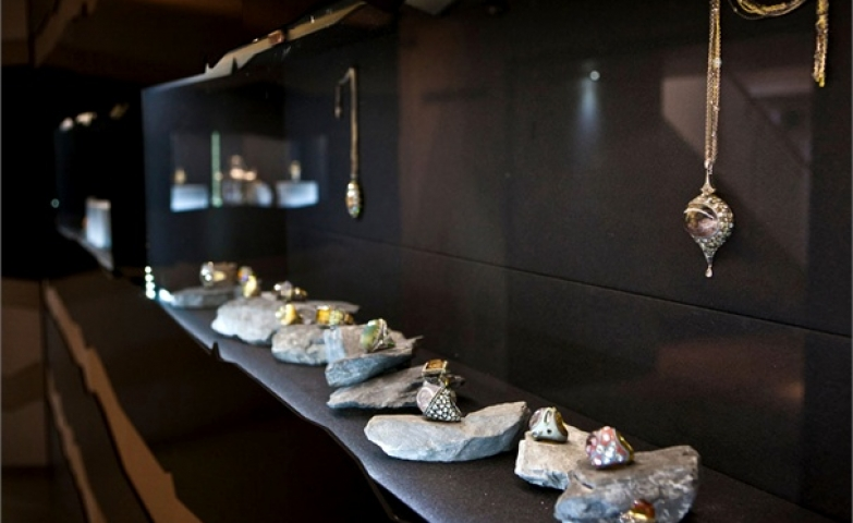 Art rock contemporary jewellery installation with pieces displayed on rocks and all black marble room. Guy Hills courtesy Shizaru.
