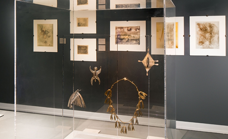 Bertoia jewelry displayed in a glass case, on glass support as to give the impression of being suspended in mid air.