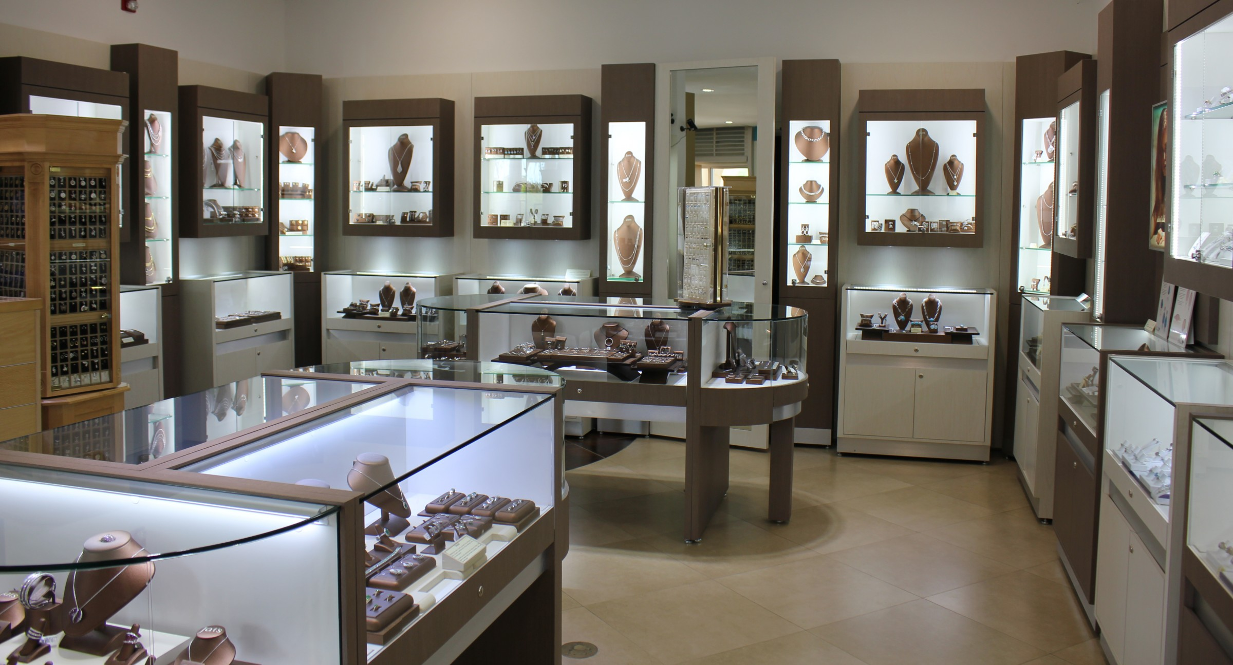 Interior setting with glass display and wall glass display - Colored Stone Merchandise.