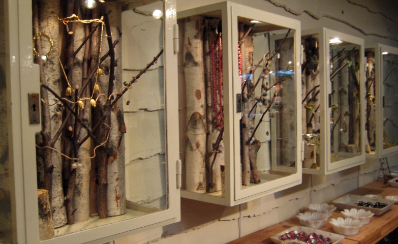 Glass cabinets with white frame and key lock, some natural tree branches added and you've got a unique display and jewellery display.