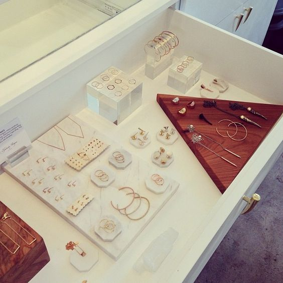 Symmetry attracts curiosity in this display with jewelry laid out on a set of drawers with glass top.