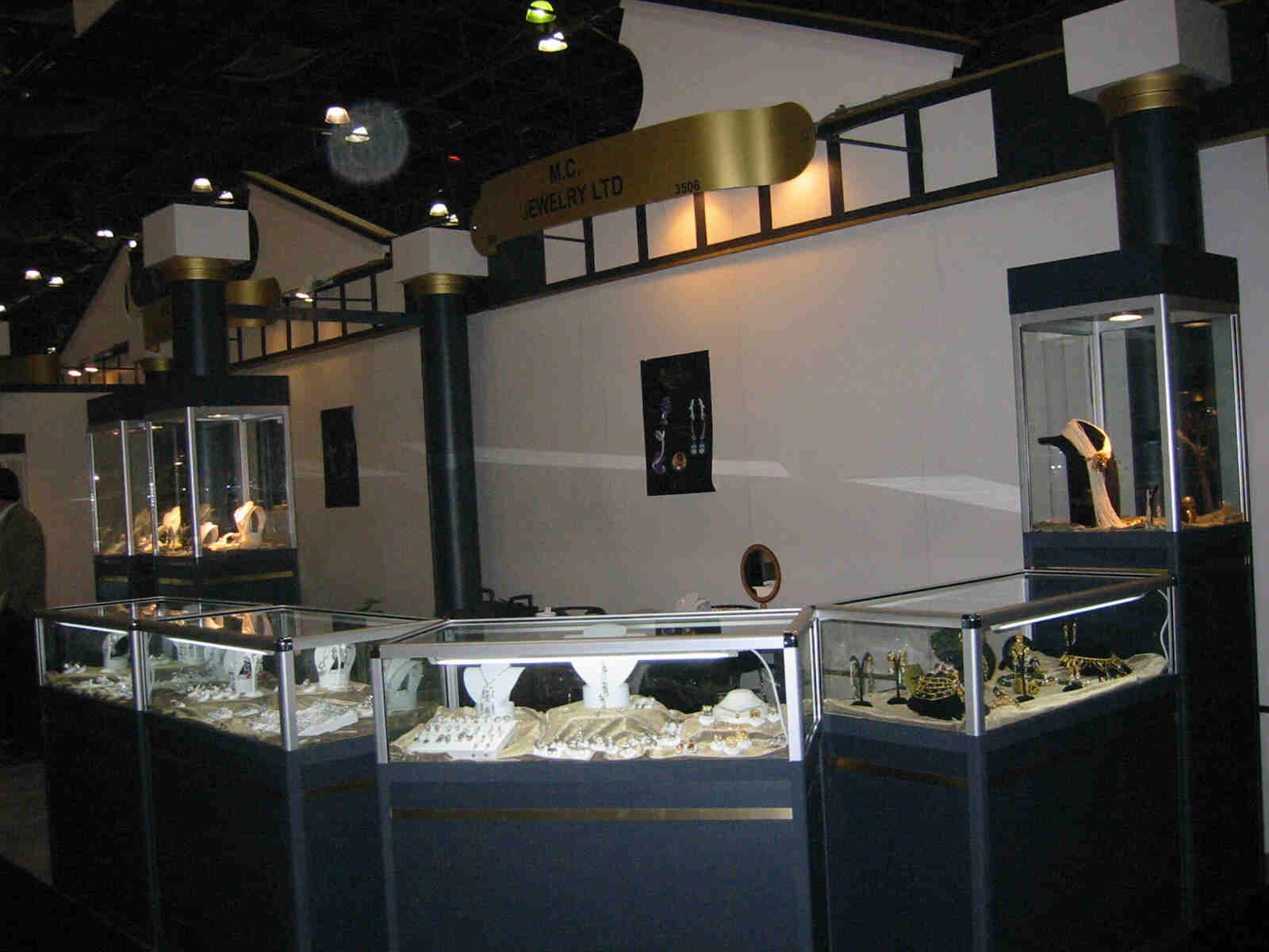 An image from Cypriot jewellers exhibit, very classic old school look. Jewels displayed in glass boxes places on dark blue stands.