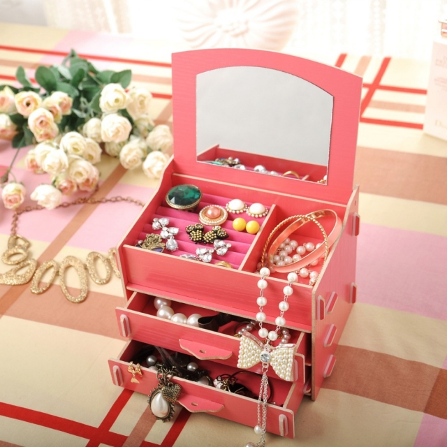 A DIY cosmetic organizer and storage box, in bright pink with drawers and interior mirror.