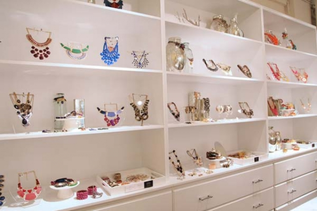 Simple white shelves with all kinds of jewelry holders and hangers, for beautiful multicolored pieces - Jewellers Magazine.