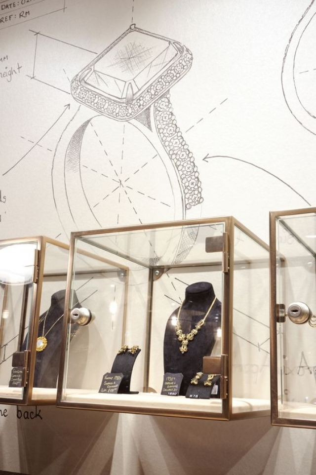 Jewellery store display idea with glass box displays and the making of a jewelry piece drawn on the wall.