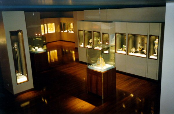 Exhibit room for jewels, placed inside white cabinets with glass box displays and also glass boxes placed on wooden stands.