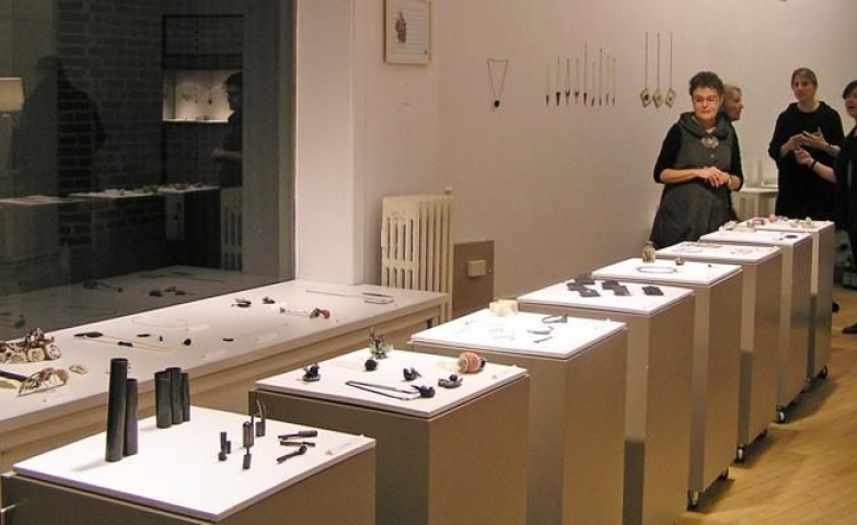 Exhibition of Israeli contemporary jewelry at the Gallery Loupe. The pieces are placed on simple white stand displays with no glass coverage.