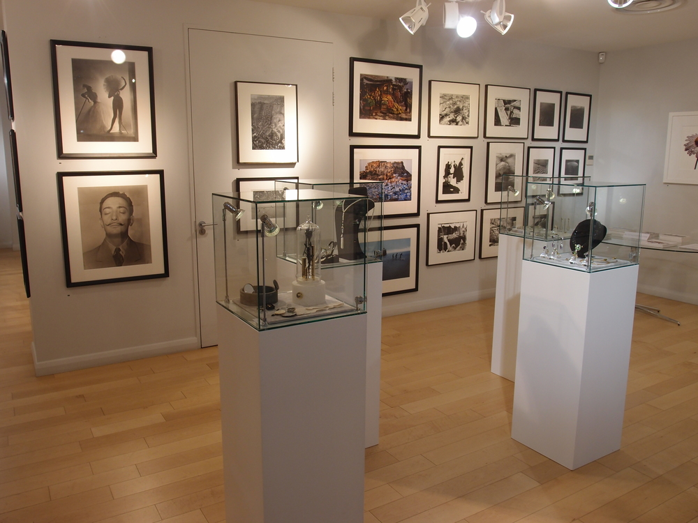 Jewelry exhibit room, walls decorated with artistic photos and illustrations and jewels displayed on white stands protected by glass boxes.