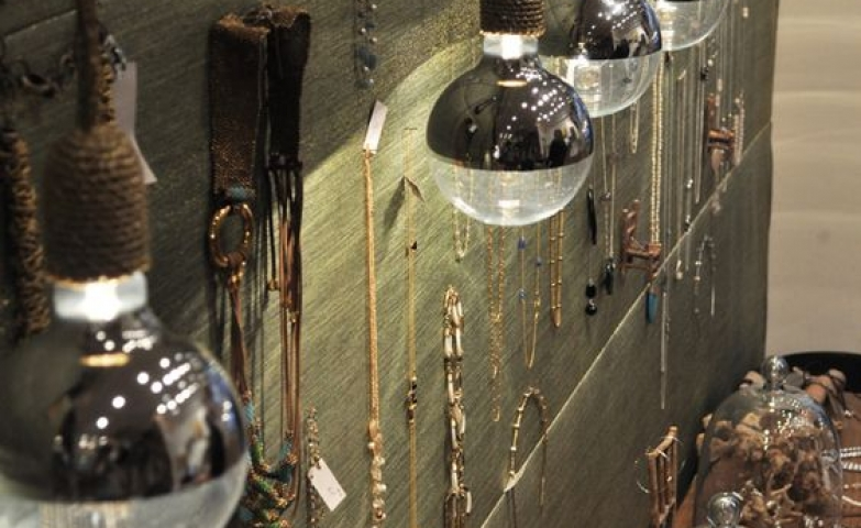 Jewelry display with pieces hanged on the wall and interesting decoration hanging light fixtures.