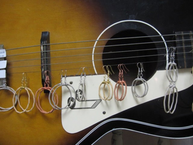A jewelry display made from a guitar and with earrings hanged on the strings.