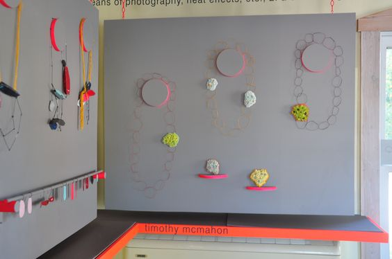 Another remarkable one from the exhibitions held at the Heidi Lowe Gallery. The display is very creative, round shaped used to hang necklaces, racks for hanging earrings, all of this combined on a grey background.