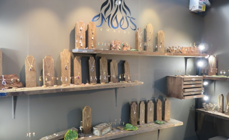 Natural looking setting with wooden necklace holders and other nature inspired decoration for a jewelry store interior visual merchandising.