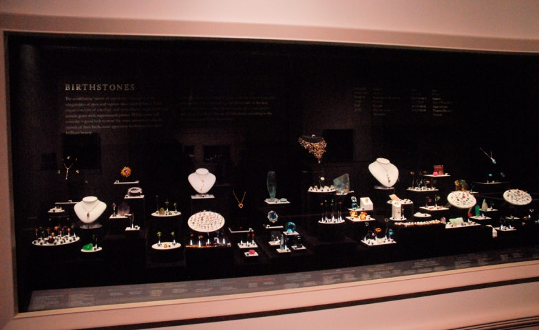 "Jewelry display set placed in a wide rectangular glass display with a dark background. The exhibit was called ""In the garden of light"" and could be seen at the Carnegie Museum of Natural History."