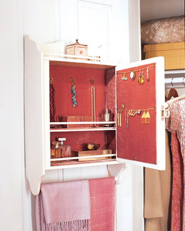 White jewelry cabinet hanged on door, with storage for jewelry and rack for scarfs.