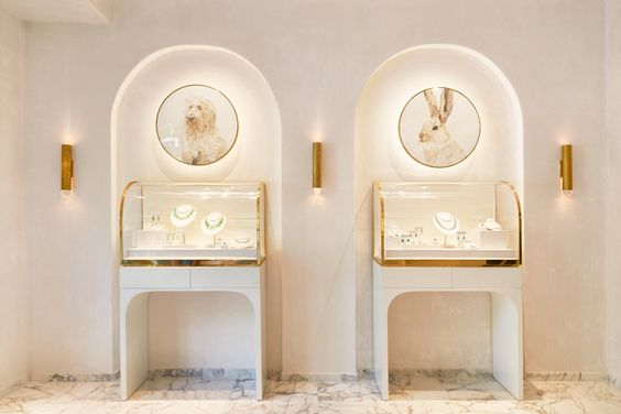 Very interesting concept for a jewelry store, combining white with discrete gold elements.