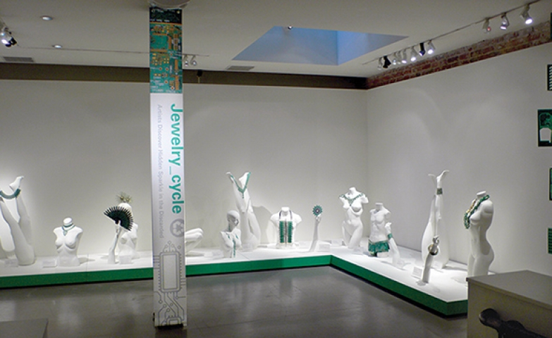 Mannequin body parts and full bodies used to display jewels at the Jewelry cycle exhibit. All white decor makes a great contrast with the vivid green details and the green jewelry pieces displayed.