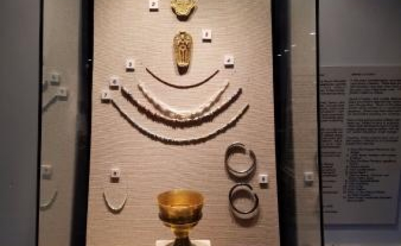 Jewelry exhibit of traditional jewel pieces and adornment. Neck pieces, bracelets and massive gold pieces presented in a tall glass box display.