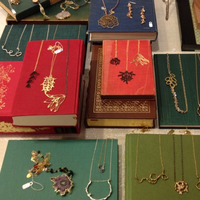Truly beautiful and unique necklaces and jewelry pieces, a merchandise jewellery display on old books.
