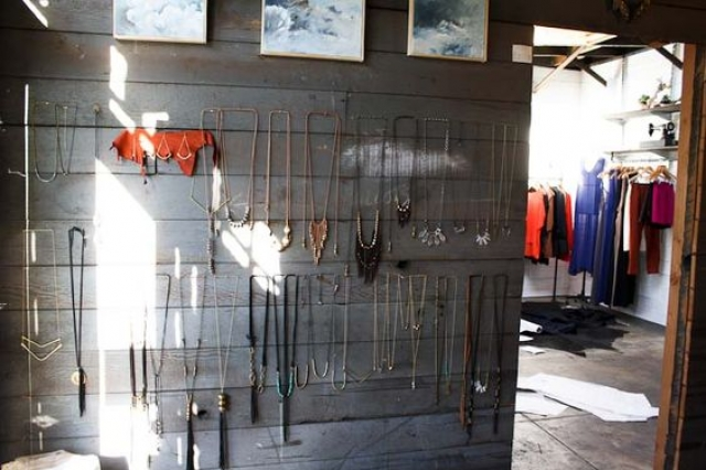Merchandise jewelry collection displayed on nails knocked into the wall and necklaces hanged on them.