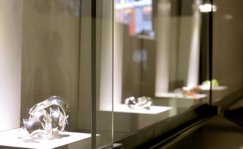 Close-up of the silver ring pieces displayed at a Linhardt Jewelry ring exhibit.