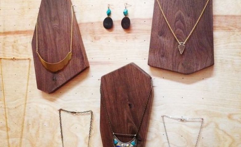 Miriam Designs jewelry display using a wooden wall with nails and wooden boards to hang necklaces.