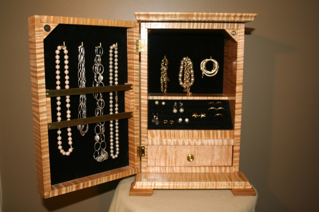 Small locking jewelry cabinet with wood finish and natural stripes.