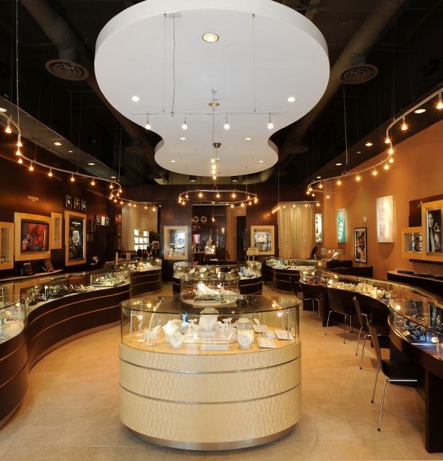 Photo from the interior of Montica jewelry store. A display island in the middle and displays on the sides.