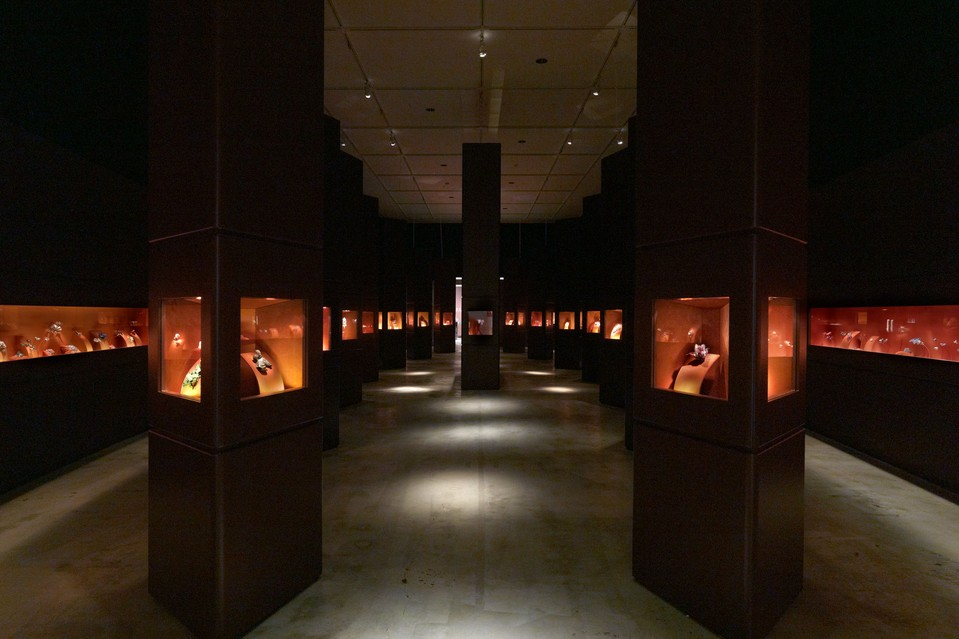 Exhibition hall giving the impression of a mirror tunnel, dark shades and minimum lights used to enhance the bright orange boxes where the jewelry pieces are displayed. From the Metropolitan Museum of Art, Jewels by Jar.