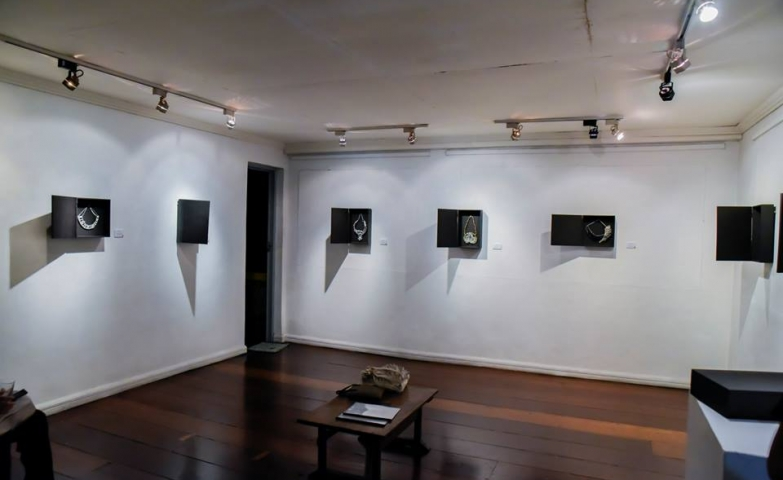Exhibition of Palamuti by PJ Valenciano. Small black boxes placed on the wall to display the jewelry pieces.
