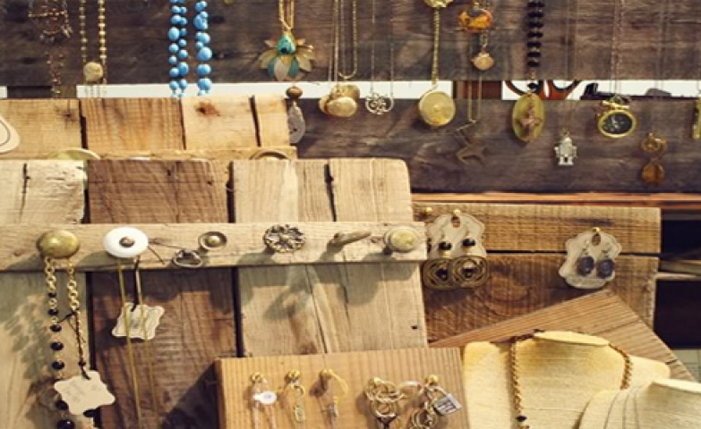 Nature look using natural wood boards with nails and knobs placed on them to hang the jewelry.