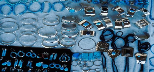 Simple blue sheet and black cloth to create a jewelry merchandising display for silver & blue stone jewels.