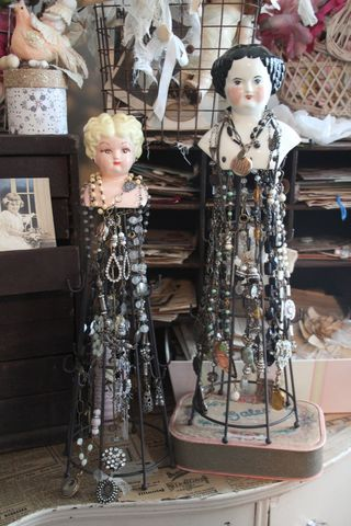 A DIY idea for visual merchandising and jewelry display is grabbing some small doll heads mounted on wire towers with wood bases.