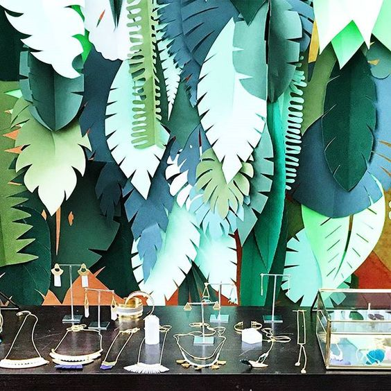 Different tones of green colored leaves used as a background for the display by Shlomit Ofir Jewelry Design.