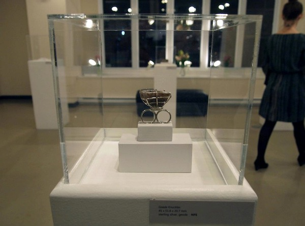 A photo of a ring jewelry piece in a glass box display from the Sinners and Saints opening by Stepehn Arsenault.