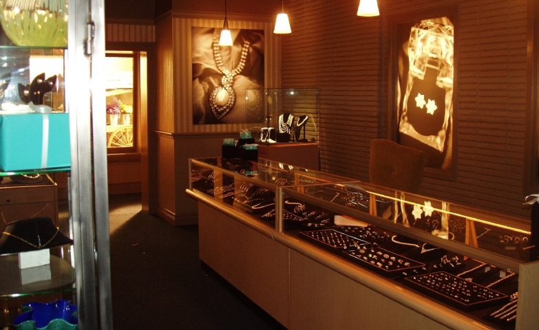 Store design with low light and illuminated pictures of jewels placed on the wall.