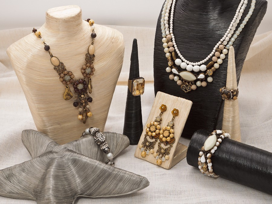 Bust, holders, hanger and rack props for a visual merchandising jewelry set display.