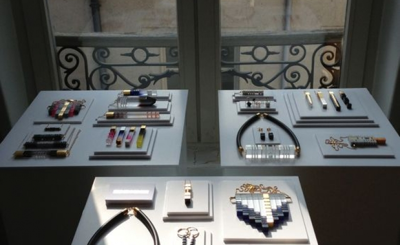 A white flat jewellery display in front of a window showing to the exterior.
