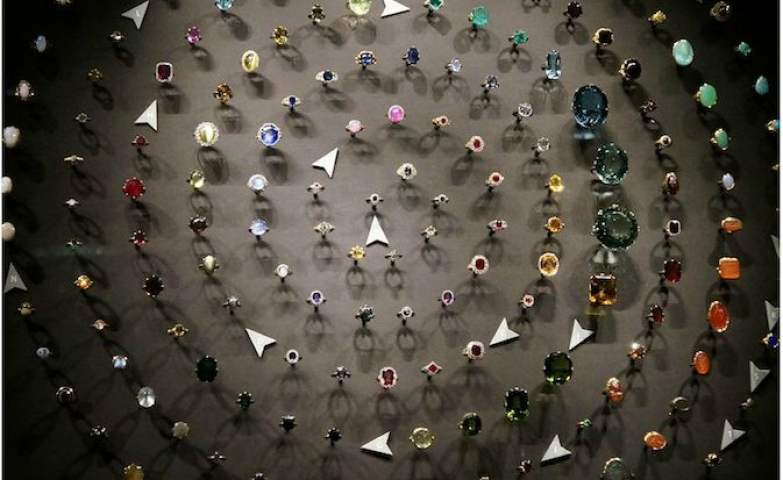A multitude of shapes, sizes and colors of rings arranged in a spiral seen at a jewelry exhibit from the V&A Museum.