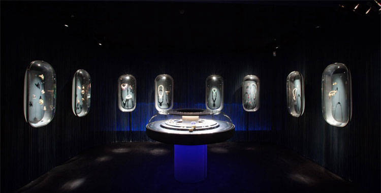 Dark royal blue, rain curtains and glass capsules used for the setting of a Van Cleef & Arpels exhibition at the Decorative Arts Museum.