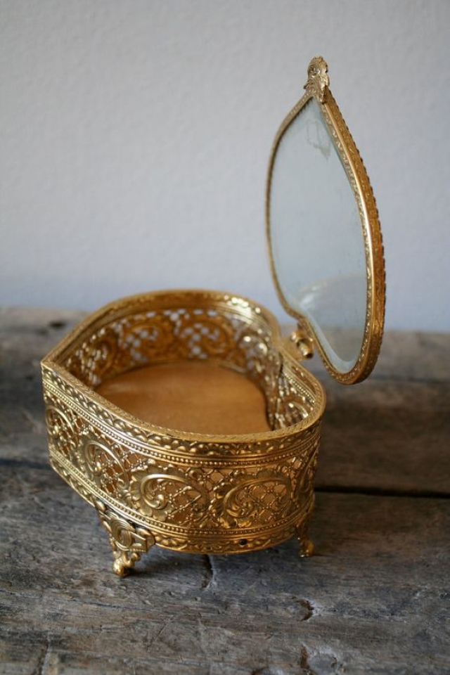 Vintage jewelry box made from metal with glass top, and an elegant gold finish.