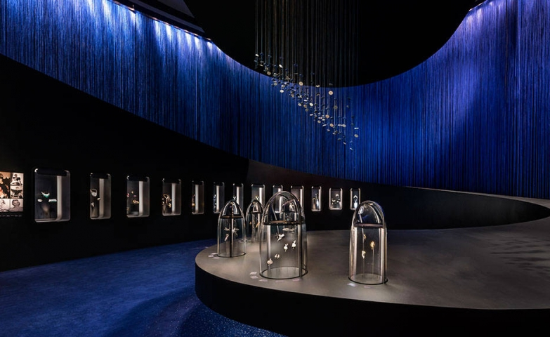 "A grey podium, royal blue rain curtains, beautiful decor hanging from the ceiling and lighted glass jewelry displays part of the exhibit ""The art & science of gems"""